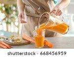 Young Woman Filling Glass Of...