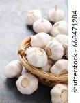garlic in basket on grey wooden ... | Shutterstock . vector #668471284