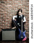 Small photo of Modern little girl in school uniform posing with electric guitar over brick wall background. Rock star, rock music, pop music concept.