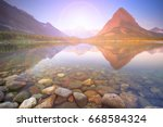 morning at swiftcurrent lake in ... | Shutterstock . vector #668584324