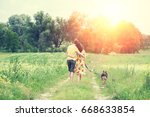 Stock photo happy couple in love with dog walking on a rural dirt road in springtime at sunset the woman and 668633854