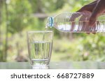 female hand pouring water from... | Shutterstock . vector #668727889