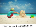 Little Boy Building Sand Castle ...