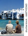 """Small photo of Couple of retired tourists admire the beautiful """"Little venice"""", the district of kora town, the main town of Mykonos island, Cyclades archipelago. ( Greece)."""