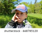 Small photo of Small boy in baseball cap blowing to the dandelion footstalk