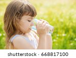 the child holds a glass of... | Shutterstock . vector #668817100