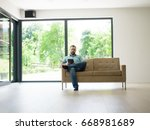 young happy man on sofa using... | Shutterstock . vector #668981689