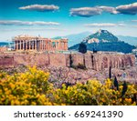 Small photo of Great spring view of Parthenon, former temple, on the Athenian Acropolis, Greece, Europe. Colorful morning scene in Athens. Traveling concept background. Artistic style post processed photo.