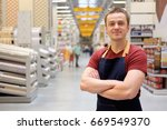 Small photo of salesman at construction super store, copy space