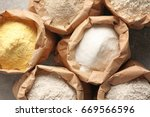 Small photo of Paper bags with different types of flour on gray background, closeup