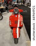 TORONTO-DECEMBER 10: Red Vespa GTS 300 Super was the super stopper for the young ladies at the Toronto Motorcycle Show on December 10, 2010 in Toronto. - stock photo