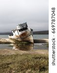 Small photo of Old Wooden Fishing Boat Aground On Beach Point Reyes California