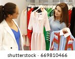 cheerful shop assistant helping ... | Shutterstock . vector #669810466