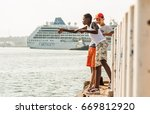 "Small photo of HAVANA - MAY 2 2016 - A couple of kids fish at Havana Bay while ""Adonia"", first american cruiser to visit Cuba in five decades, finishes the docking maneuvers."