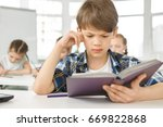 Small photo of Young adorable boy concentrating while reading a book during lesson copyspace studying learning education children childhood smart clever intelligence literature pupil learner elementary school