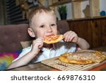 the boy is eating pizza | Shutterstock . vector #669876310