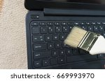 cleaning keyboard with brush | Shutterstock . vector #669993970