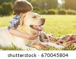 young boy hugging his dog at...   Shutterstock . vector #670045804