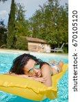 Small photo of Enjoying suntan. Vacation concept. Slim young woman in bikini on the yellow air mattress in the swimming pool.