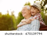 Stock photo shot of a happy senior man smiling looking away his grandson hugging him from behind copyspace 670139794