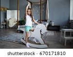 cute little girl riding a toy... | Shutterstock . vector #670171810