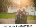 elderly couple with garden hose.... | Shutterstock . vector #670179010