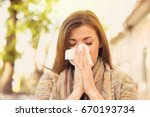 Small photo of Woman with allergy symptoms blowing nose