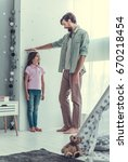 handsome young dad is measuring ... | Shutterstock . vector #670218454