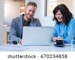 two smiling work colleagues... | Shutterstock . vector #670234858
