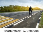 Small photo of Cyclist on the track. A horizontal. A figure of a man on a bicycle moving into the distance in perspective from left to right along an asphalt canvas with yellow and white markings