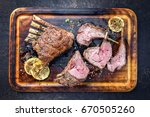 Small photo of Barbecue Leg of Lamb and Rack as top view on burnt cutting board