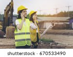 Small photo of Two beautiful young engineers who use Smartphones to liaise in large building construction projects.
