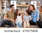 happy family sitting on sofa in ... | Shutterstock . vector #670575808