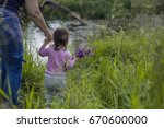 toddler girl holding her... | Shutterstock . vector #670600000