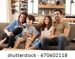 family sitting on sofa in open... | Shutterstock . vector #670602118