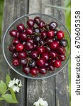 bowl with fresh cherries on old ... | Shutterstock . vector #670605358