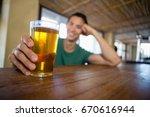 smiling man holding beer glass... | Shutterstock . vector #670616944