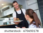 waiter serving customer at... | Shutterstock . vector #670650178