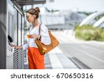 young woman buying a ticket for ... | Shutterstock . vector #670650316