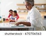 senior woman looking at recipe... | Shutterstock . vector #670706563