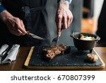 man slicing cooked medium rib... | Shutterstock . vector #670807399