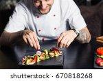 male cooks preparing meat in... | Shutterstock . vector #670818268