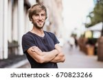 Stock photo handsome smiling young man portrait cheerful men looking at camera 670823266