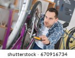 business owner repairing bicycle | Shutterstock . vector #670916734