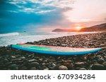 surfboard on a stones beach... | Shutterstock . vector #670934284