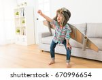 Small photo of smiling sweet female children wearing astronaut costume making ready to fly gesture standing on living room wooden floor at home.