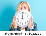 Young Woman Holding A Clock...