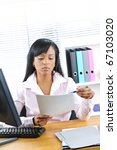 Stock photo young black business woman reading document at desk in office 67103020