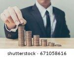 businessman hand putting coin... | Shutterstock . vector #671058616