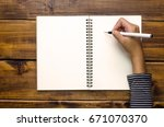 hands are writing in a notebook ... | Shutterstock . vector #671070370
